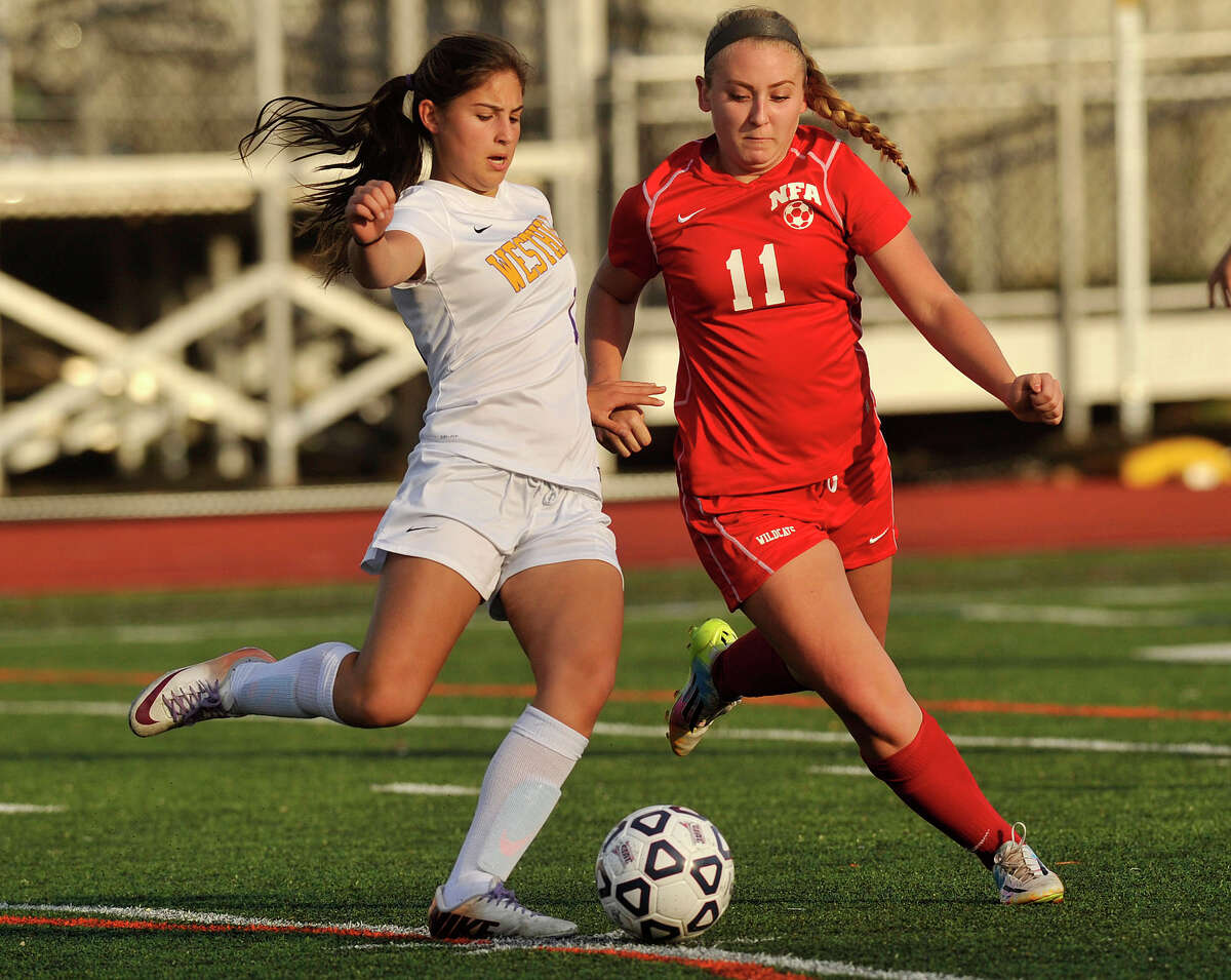 Westhill's Maria Elizathe passes the ball while under pressure from NFA's Maegan Phipps during their Class LL state tournament game at Westhill High School in Stamford, Conn., on Tuesday, Nov. 4, 2014. Westhill won, 6-0.