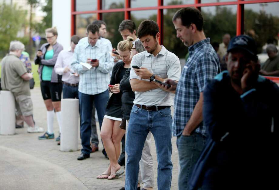 A new app could point voters like these to the closest voting center rather than their precinct. Photo: Gary Coronado, Houston Chronicle / © 2014 Houston Chronicle