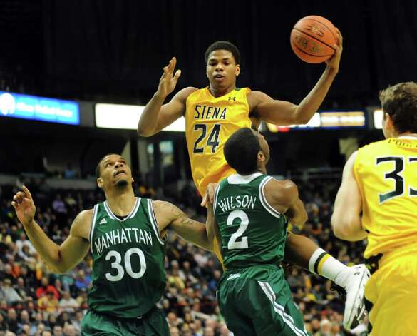 Siena's Lavon Long, center, gains air as Manhattan's Ashton Pankey, left, and Tyler Wilson defend during their basketball game on Friday, Feb. 21, 2014, at Times Union Center in Albany, N.Y. (Cindy Schultz / Times Union) Photo: Cindy Schultz / 00025724A