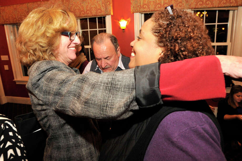 Julia Wade, left, and Betsy Allyn, right, candidates for seats on the Board of Education, embrace as John Mallozzi, chair of the Stamford Democrats, looks up vote numbers during the Democrat Party election night celebration at Zody's 19th Hole at E. Gaynor Brennan Golf Course in Stamford, Conn., on Nov. 4, 2014. Photo: Jason Rearick / Stamford Advocate