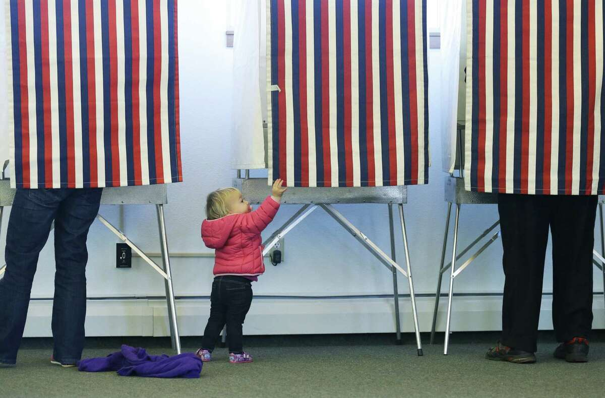 Zoe Buck, 14 months, checks out an empty voting booth as her mother, Julie Buck, votes on the left Tuesday at a polling site at the Alaska Zoo in Anchorage.