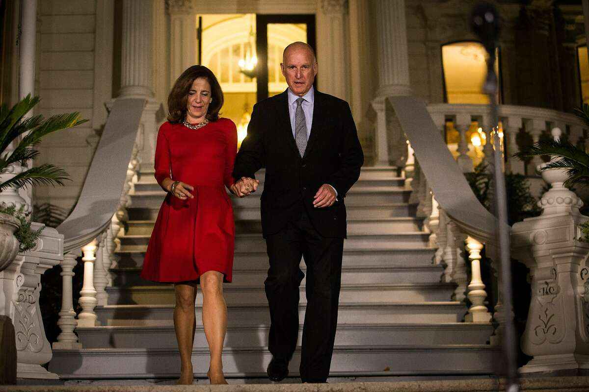Gov. Jerry Brown, with Anne Gust Brown, walks to speak to the media after being reelected to a fourth term in front of the Governor's Mansion in Sacramento, California, November 4, 2014.