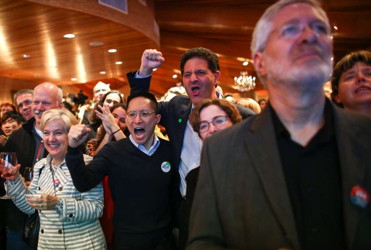 Nick Hanauer, center, who helped back Initiative 594, cheers with others during an Initiative 594 return watching party at the Edgewater Hotel in Seattle. The initiative will require mandatory background checks for firearms sales. Photographed on Tuesday, November 4, 2014. (Joshua Trujillo, seattlepi.com)