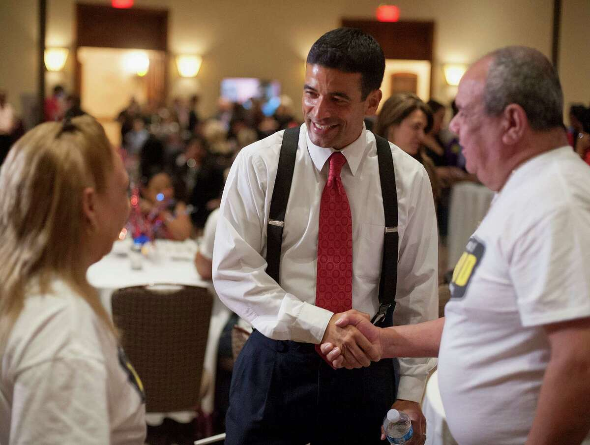 District attorney candidate Nico LaHood, center, greets supporters Jose Tovar, right, and wife Lucia Tovar, during LaHood's election night event, Tuesday, Nov. 4, 2014, in San Antonio.