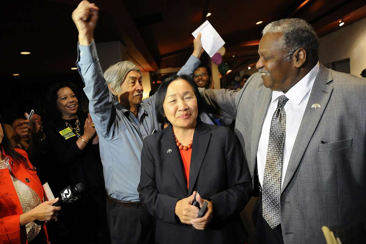 Mayor Jean Quan and her husband Floyd Huen, left, are greeted by her campaign chair Sandre Swanson, right, as they arrive to the election night party for incumbent Oakland Mayor Jean Quan held at Scott's Seafood Restaurant in Oakland, CA, on Tuesday, November 4, 2014.