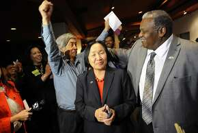 Mayor Quan and her husband Floyd Huen, left, are greeted by her campaign chair Sandre Swanson, right, as they arrive to the election night party for incumbent Oakland Mayor Jean Quan held at Scott's Seafood Restaurant in Oakland, CA, on Tuesday, November 4, 2014.