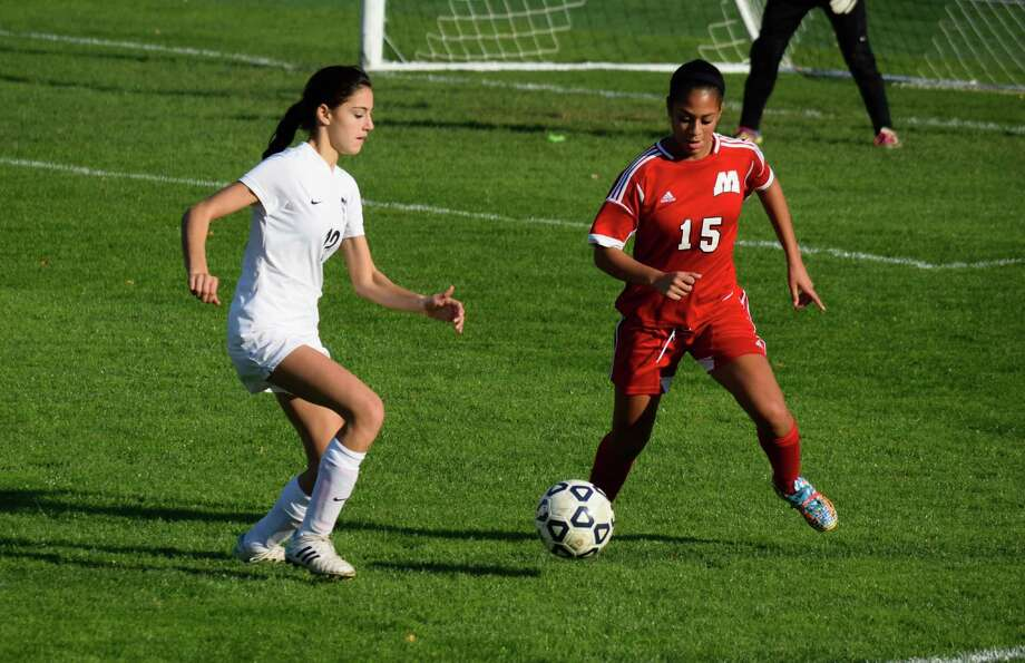 Staples sophomore Ivy Prince, left, goes for a ball against Manchester's Stephanie Sanchez in the teams' Class LL first round game on Tuesday. Staples won 4-0. Photo: Contributed Photo / Westport News Contributed