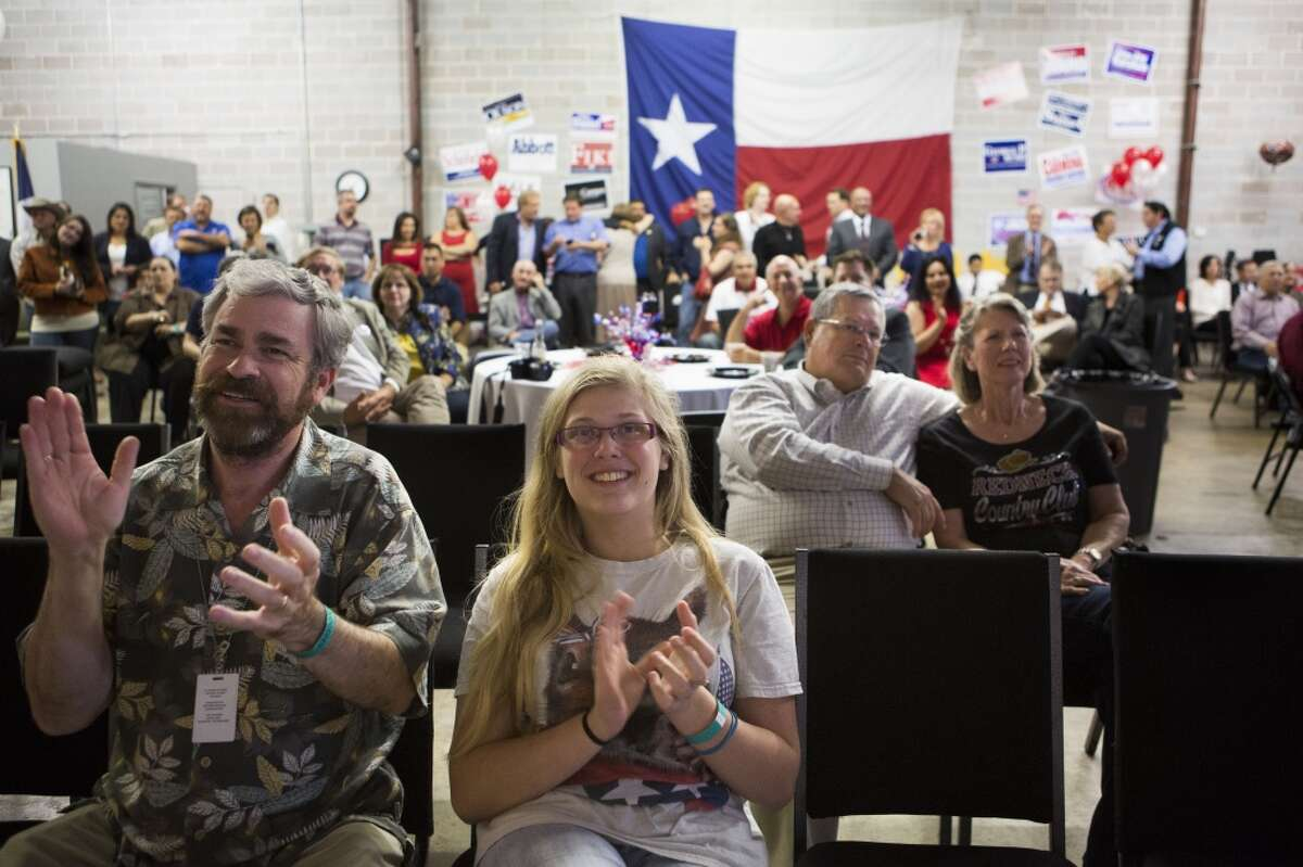 Kameron Searle, left, and his daughter, Kayla, 16, celebrate the Republicans' victories in Houston.