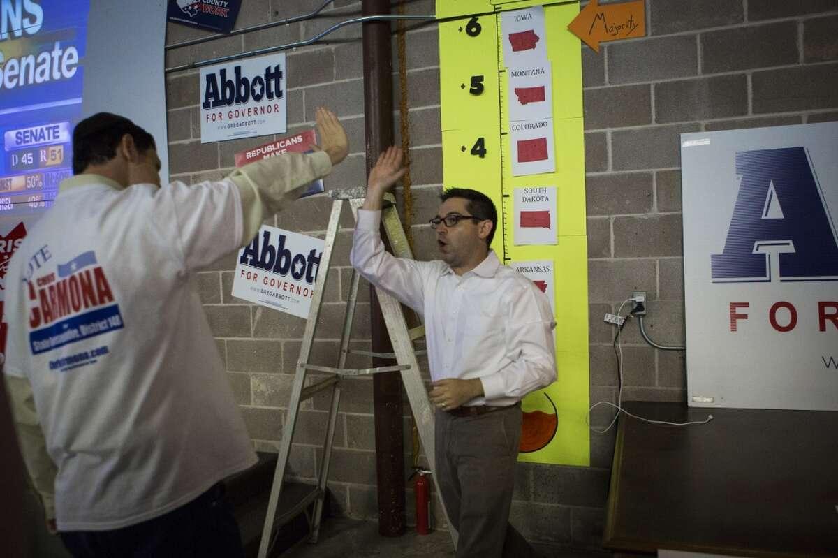 Harris County Republican Party staffer Ben Stinsman high-fives volunteer David Gratvol, 28.