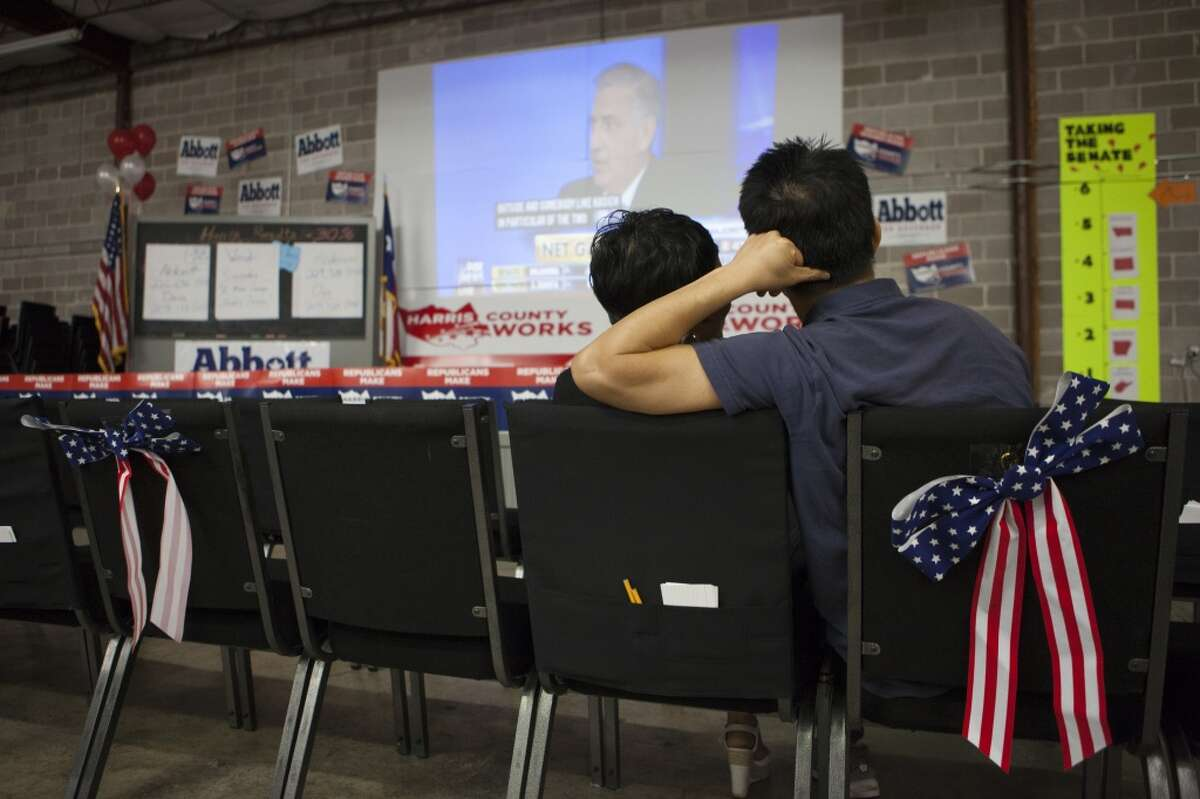 A couple watches election results from the Harris County Republican Party watch gathering in Houston.