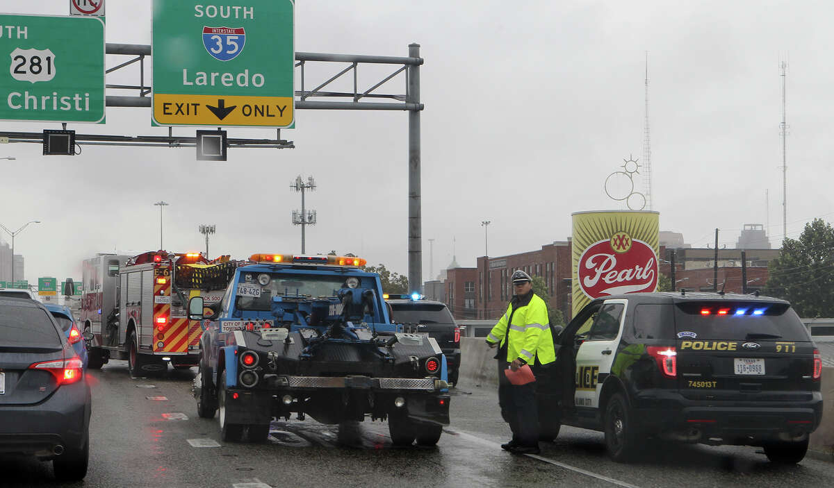 San Antonio police, fire and a wrecker crew clear an accident scene Wednesday November 5, 2014 on U.S. Highway 281 southbound near Grayson street that involved a San Antonio police officer. Traffic is backed up in the area and no serious injuries were reported.