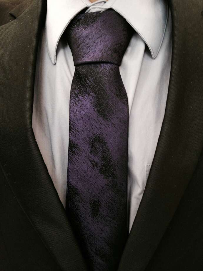 Because Todd Solis is partial to wearing a dark suit he expresses his personal style with colorful accessories such as this purple tie with a black smudgy print. Photo: Express-News / San Antonio Express-News