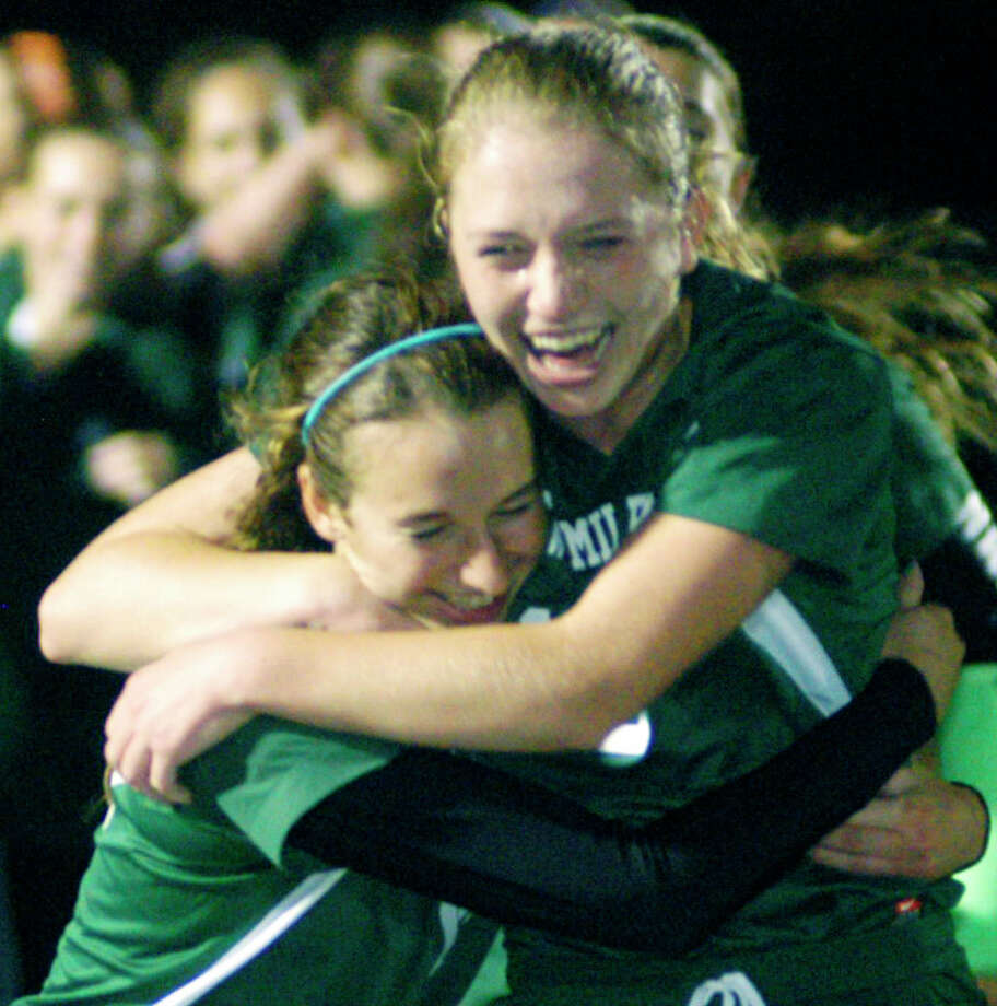 Fellow Green Wave seniors Gigi Fusco and Helen Bayers, right, lead the celebration seconds after the final horn of New Milford High School's 2-1 victory over Masuk in the South-West Conference girls' soccer title match at Newtown High. Oct. 29, 2014 Photo: Norm Cummings / The News-Times