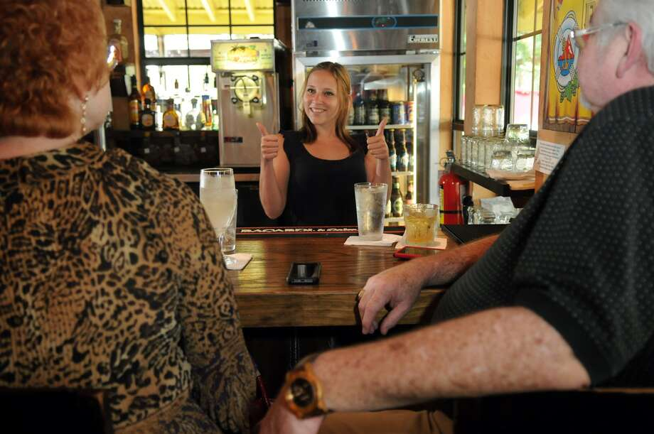 Bartender Tiffany Caudill, 26, center, of Hockley, talked to customers Vicky and Randy Cosby, of Magnolia, at Cisco's Salsa Company in Tomball this summer. The local business and other downtown merchants are worked to repeal a 70-year-old dry ordinance that limited the amount of alcohol served in downtown Tomball. Photo: Jerry Baker, Freelance