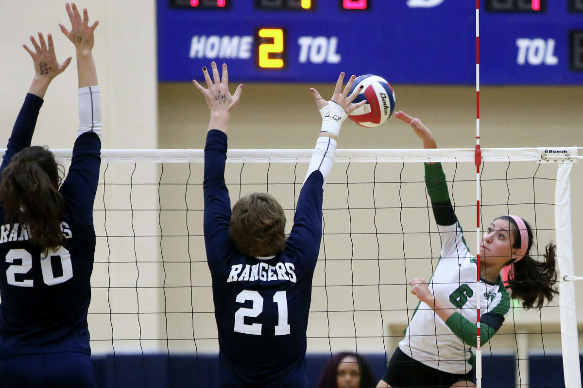 Reagan's Elissa Barbosa (far right) tries to get a spike past Smithson Valley's McKinlee Boss ande Kaihan Williams during a Class 6A first-round volleyball playoff match at the Alamo Convocation Center on Nov. 4, 2014.