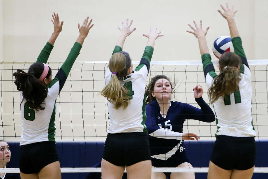 Smithson Valley's Victoria Bibbens (15) tries to get a shot past Reagan's Elissa Barbosa (from left) Mackenna Wollet and Camryn Ennis during their UIL Class 6A first-round volleyball playoff match at Alamo Convocation Center on Nov. 4, 2014. Photo: Marvin Pfeiffer /San Antonio Express-News / Express-News 2014