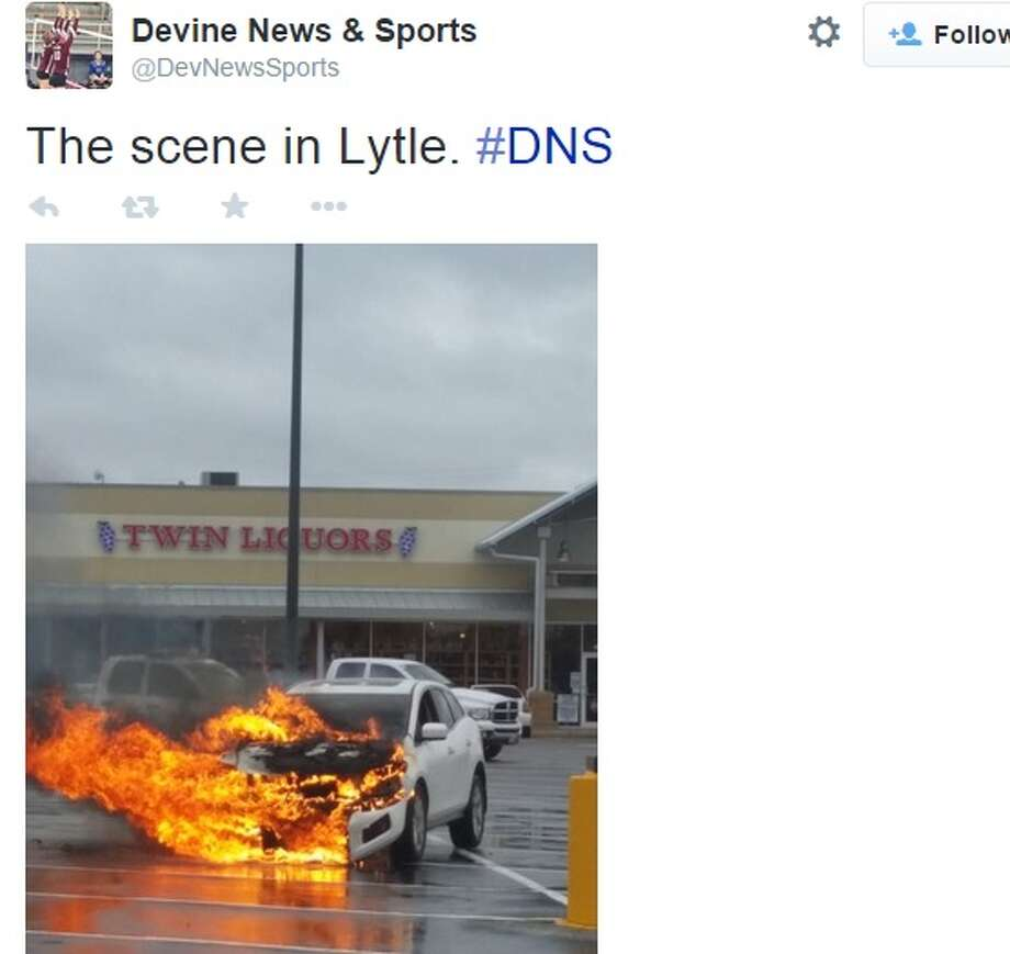 A white SUV completely engulfed in flames in the parking lot of an H-E-B in Lytle Wednesday. Photo: Twitter, Courtesy