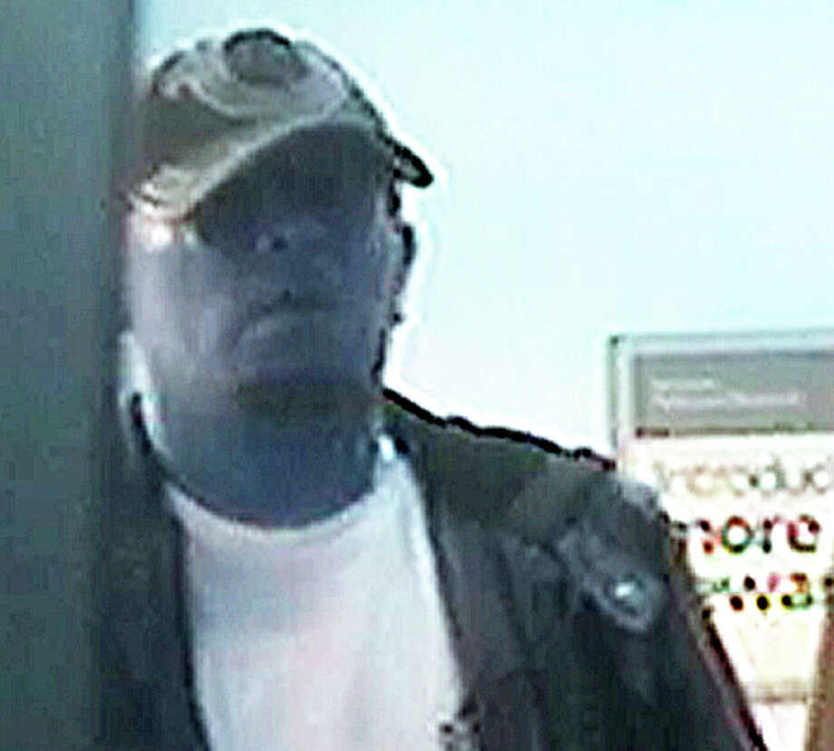 This man, recorded in a surveillance video at a local branch of Bank of America, is sought for his role in forcing a Fairfiedl man to withdraw all his money from an account at the bank Photo: Fairfield Police Department / Fairfield Citizen