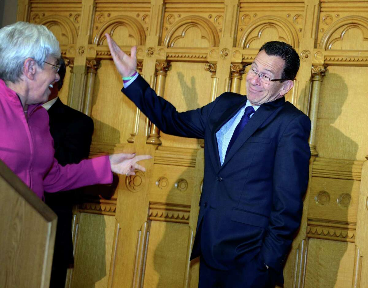 Gov. Dannel P. Malloy and Lt. Gov. Nancy Wyman react to a room full of applause from supporters Wednesday, Nov. 5, 2014, during a news conference at the State Capitol in Hartford, Conn.