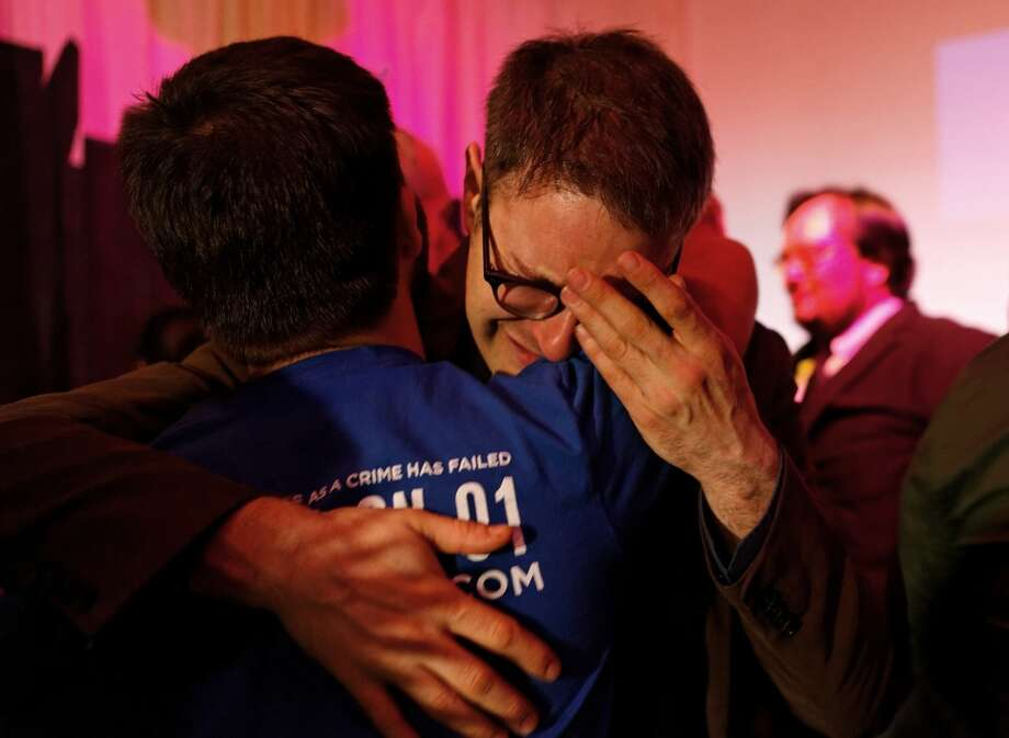 Oregon legalized it in the 2014 November elections and created the basic framework for a  legal marijuana market in that state, Photo: Peter Zuckerman, who handled publicity for Ballot Measure 91, which legalizes the recreational use of marijuana in Oregon, hugs a supporter of the measure after it passed Tuesday, Nov. 4, 2014, at Holocene night club in Portland, Ore. (AP Photo/The Oregonian, Madeline Stone)   Photo: Madeline Stone, AP