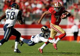 San Francisco 49ers' Colin Kaepernick tries to escape a tackle attempt by St. Louis Rams' Trumaine Johnson in 2nd quarter of Rams' 13-10 loss during NFL game at Levi's Stadium in Santa Clara, Calif., on Sunday, November 2, 2014.