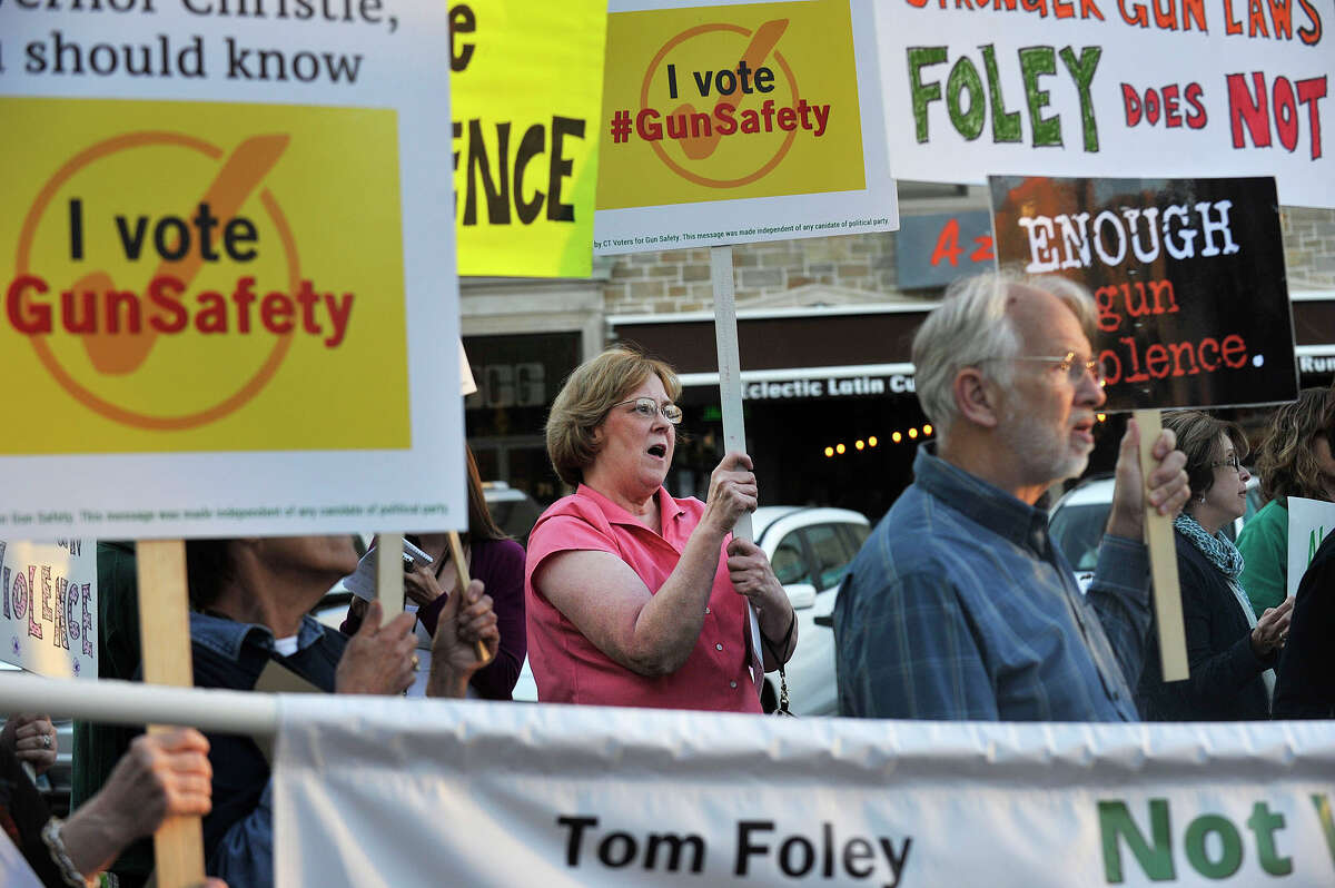Ellen Letkowski, center, with Newtown Action Alliance, a gun control group, protests New Jersey Gov. Chris Christie's visit to Stamford while he stumps for Connecticut gubernatorial candidate Tom Foley outside Bobby V's Sports Bar in Stamford, Conn., on Tuesday, Sept. 23, 2014.