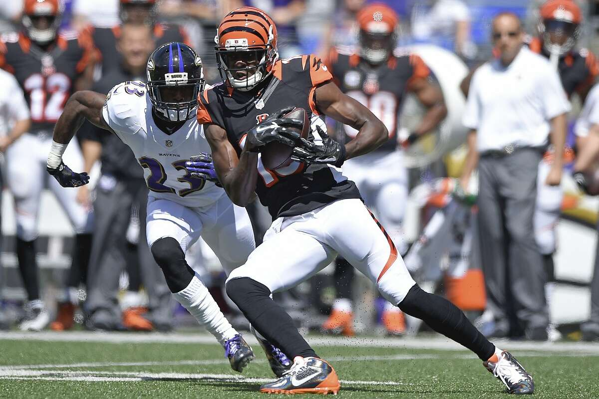 Cincinnati Bengals wide receiver A.J. Green (18) carries the ball under pressure from Baltimore Ravens defensive back Chykie Brown (23) during the first half of an NFL football game in Baltimore, Md., Sunday, Sept. 7, 2014. (AP Photo/Nick Wass)