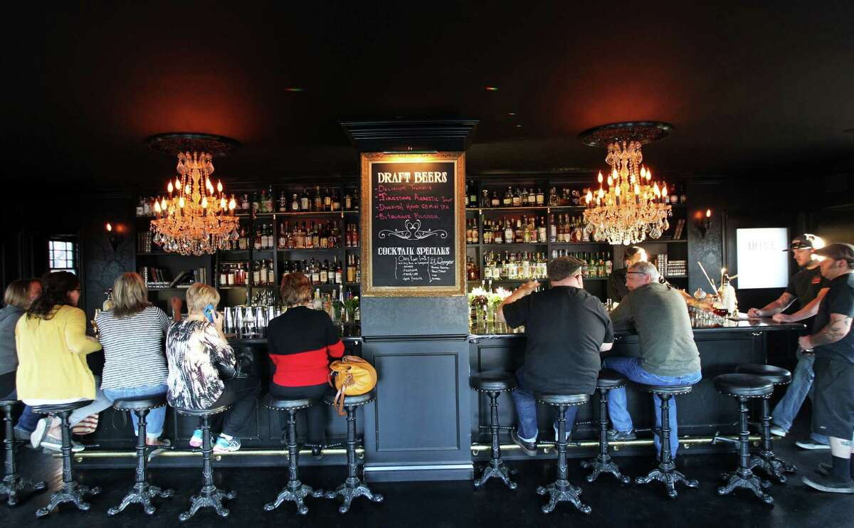 Visitors to Death & Taxes in Reno's Midtown area relax in a refined interior with a Victorian feel at one of the spots reinvigorating the city's cultural aesthetic.