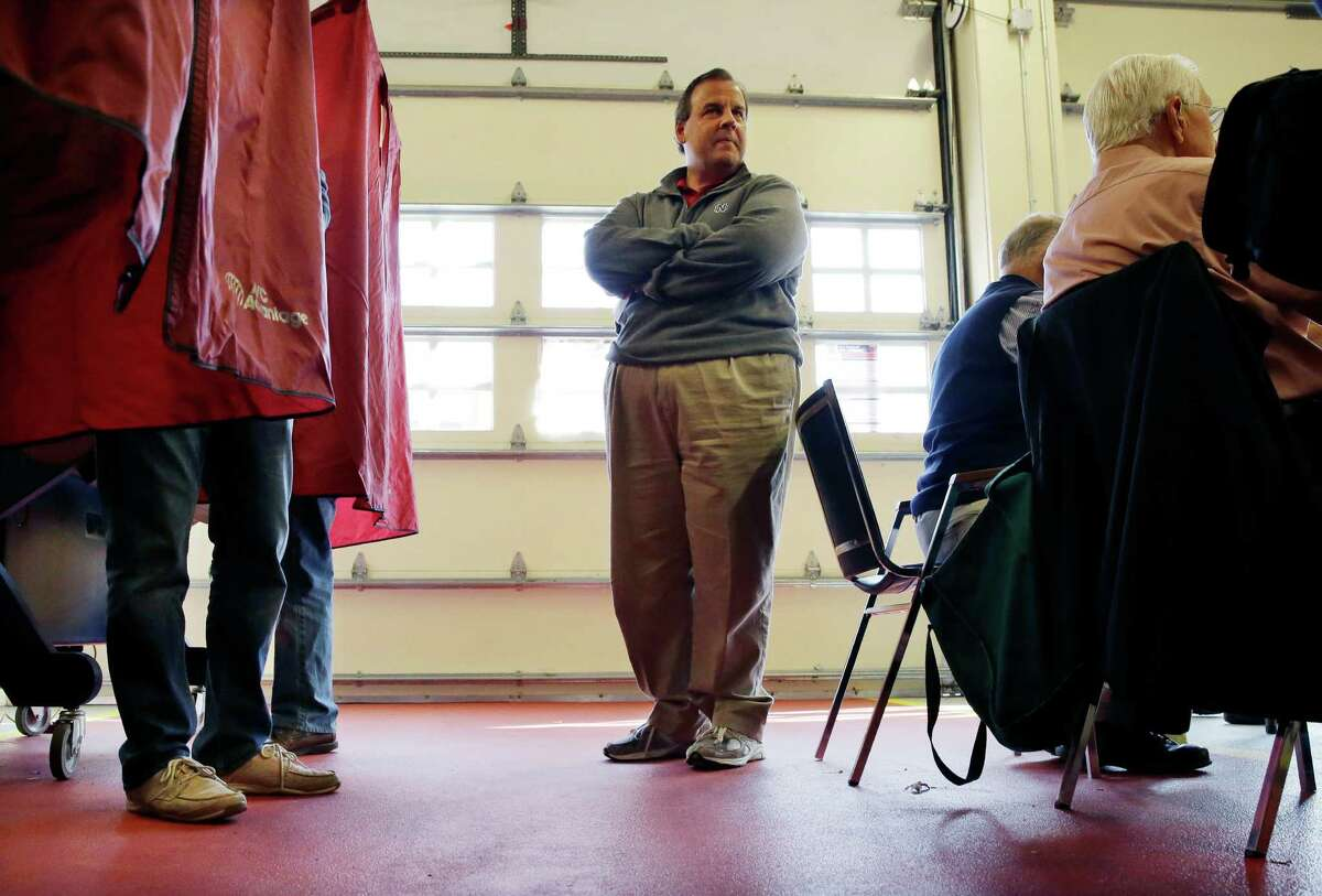 New Jersey Gov. Chris Christie waits in line to vote on Election Day. A reader says he is starting to view the governor as a presidential contender who could bridge the vast gulf between Republicans and Democrats.