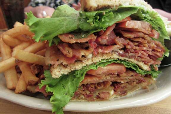 JUST BACON A LIVING is the name of the BLT served at Kenny & Ziggy's New York Delicatessen on Post Oak Boulevard. The triple decker sandwich includes a pound of of crisp bacon, lettuce and tomato and is served on white toast.  Shot October 2014.