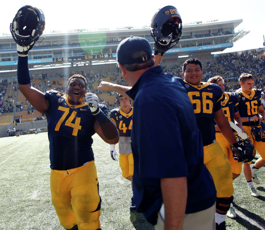 Cal head coach Sonny Dykes celebrates with Matt Cochran (74) after the Bears' 55-14 win over Sacramento State at Memorial Stadium on Sept. 6, 2014. Photo: Scott Strazzante / The Chronicle / ONLINE_YES