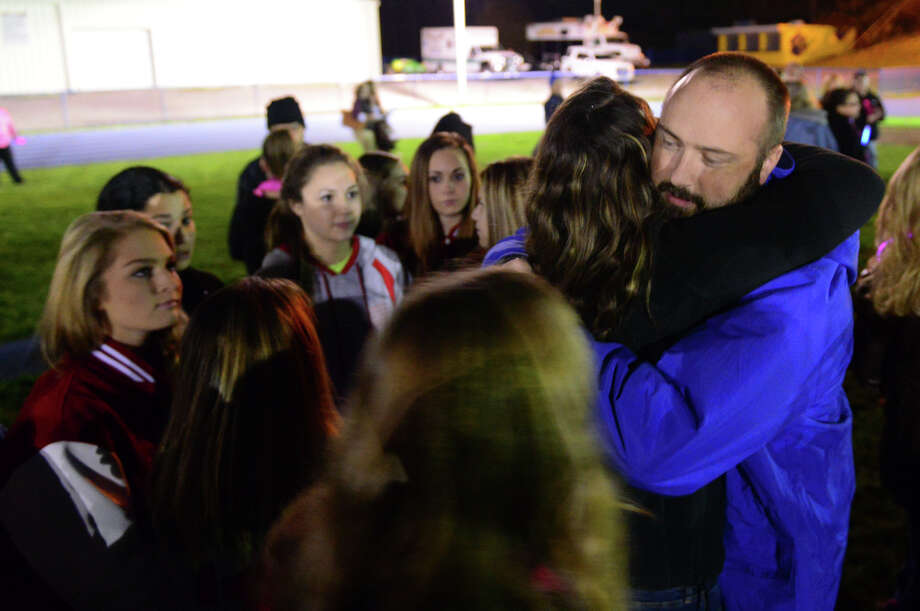 "Darrell Scheck hugs members of the Derby High School cheerleading team during Seymour High School's ""Walk of Light Vigil,"" held for student Nina Poeta in Seymour, Conn., on Wednesday November 5, 2014. Nina, a Seymour High School cheerleader, lost her battle against cancer last week. Photo: Christian Abraham / Connecticut Post"