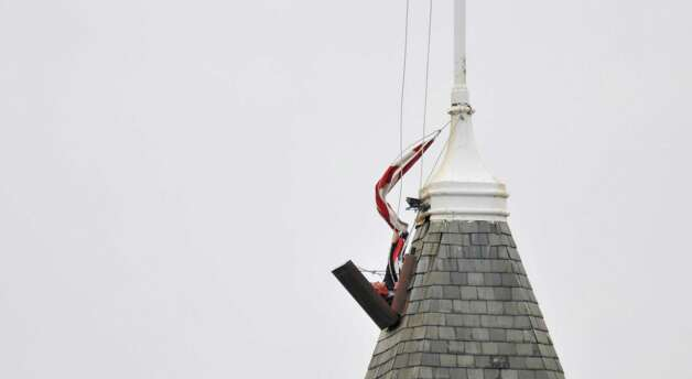 Steve Valigorsky, a roofer and owner of Quality Roofing, pulls an old flag down that was on top of the Cohoes City Hall building on Wednesday, Nov. 5, 2014, in Cohoes, N.Y.  The flag is replaced about every three months.  (Paul Buckowski / Times Union) Photo: Paul Buckowski / 00029338A