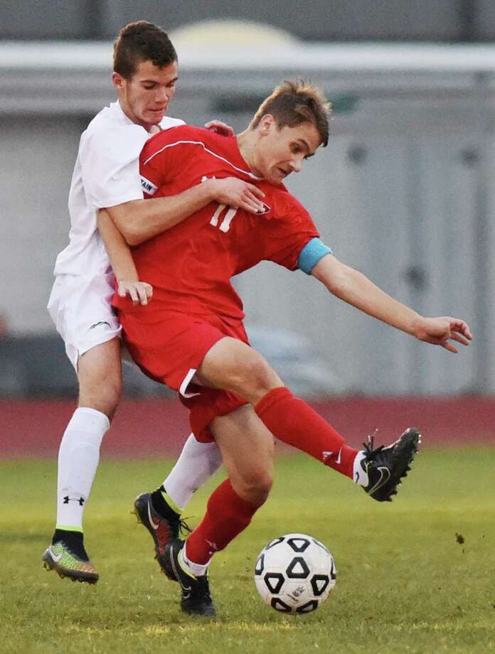 New Milford's Adrian Lekaj, left, defends Greenwich's Daniel Ozizmir in Greenwich's 3-1 win over New Milford in the CIAC Class LL boys soccer second round game at New Milford High School in New Milford, Conn. Wednesday, Nov. 5, 2014. Photo: Tyler Sizemore / Greenwich Time