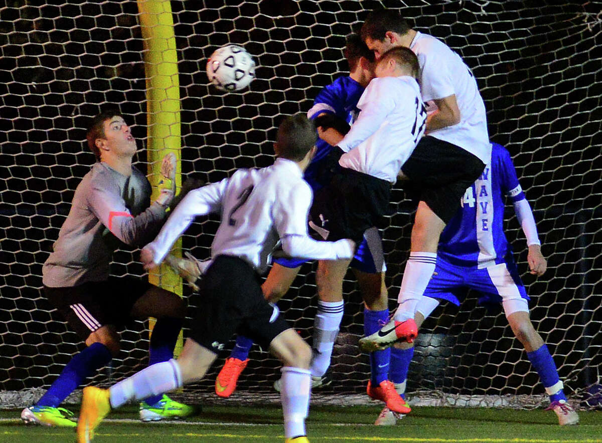 Darien goalie Liam Rischmann, left, goes to make a stop, during Class LL 2nd round of boys soccer action against Shelton in Shelton, Conn., on Wednesday Nov. 5, 2014.