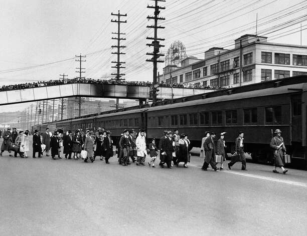 Seattle crowds jam an overhead walk to witness the exile of Japanese Americans from Bainbridge Island, the first of 120,000 people of Japanese ancestry in the country incarcerated under Executive Order 9066. This group was heading to the Manzanar camp in California. Photo: AP / 1942 AP