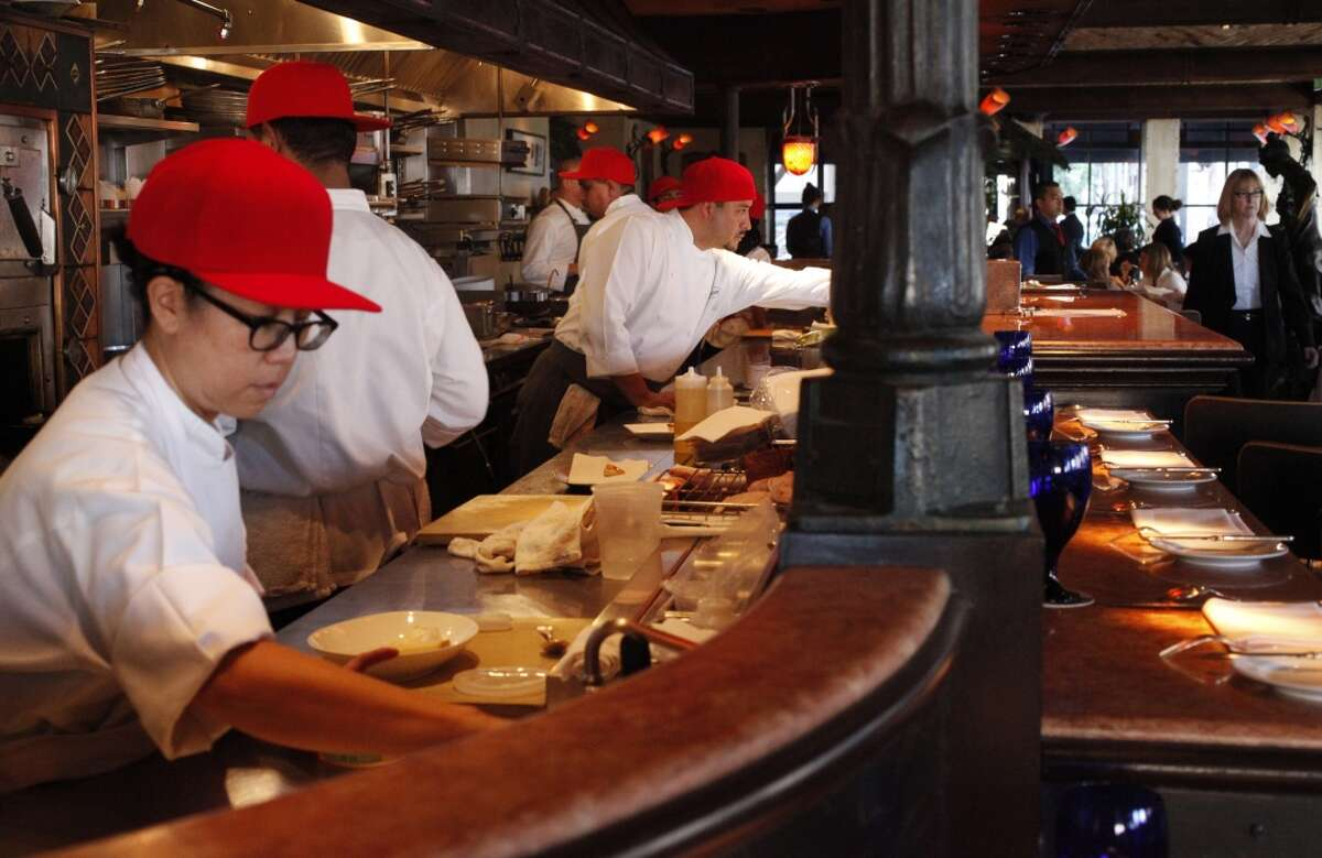Pastry cook Lisa Chan, left, wears a red hat with the line cooks, from left of her, Edgar Martinez, and Alex Martinez in celebration of Love Local SF Nov. 5, 2014 at the Boulevard restaurant in San Francisco, Calif.
