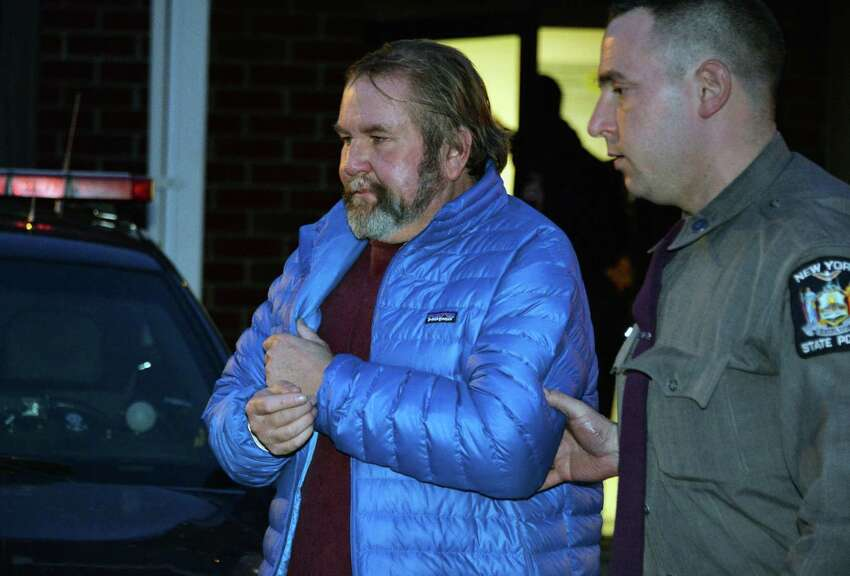 Saratoga County-based blogger John Tighe of Milton is lead from Clifton Park Town Court by NYS Police after his arraignment on child pornography charges Wednesday, Feb. 26, 2014, in Clifton park, N.Y. (John Carl D'Annibale / Times Union)