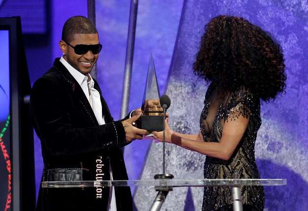 "LOS ANGELES, CA - NOVEMBER 14:  Singer Usher accepts his award for ""Favorite Male Artist- Soul/Rhythm & Blues"" from singer Diana Ross on stage during the 32nd Annual ""American Music Awards"" at the Shrine Auditorium November 14, 2004 in Los Angeles, California.  (Photo by Frank Micelotta/Getty Images) Photo: Frank Micelotta, Getty Images / 2004 Getty Images"