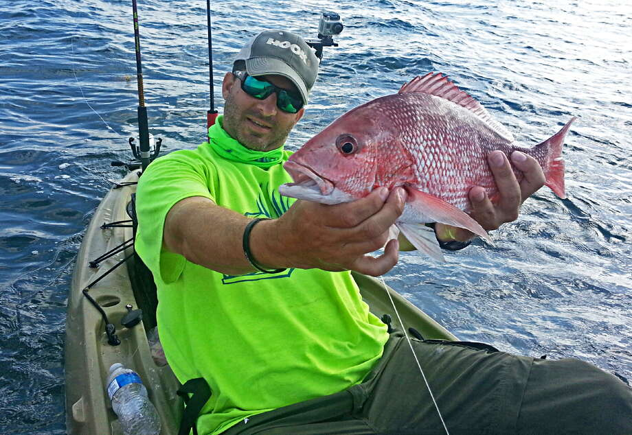 "Leaning back in his kayak, Ty Southerland talks about this red snapper he just reeled in for ""30 Miles Out"" on YouTube. Photo: John Goodspeed / John Goodspeed / For The Express-News"