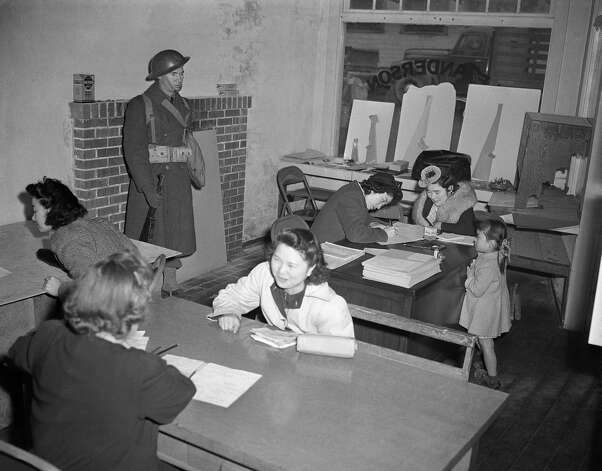 Japanese residents of Bainbridge Island, near the Puget Sound, Wash., Navy yard, register while a soldier stands guard, March 25, 1942. All Japanese were ordered evacuated from Bainbridge Island. Photo: Paul Wagner, AP / AP1942