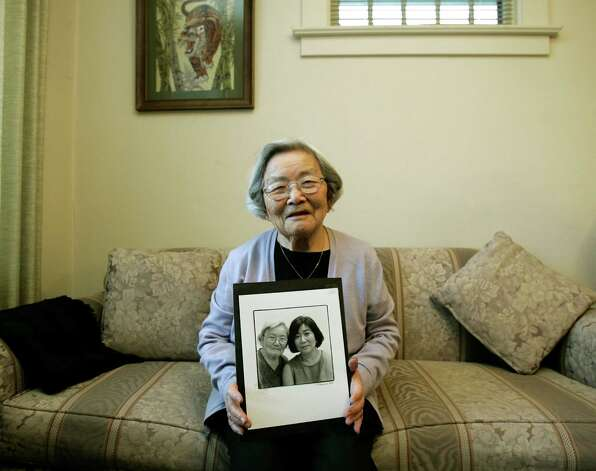 Fumiko Hayashida holds a photo of herself and daughter K. Natalie Ong on Feb. 6, 2007, the day the U.S. House approved a plan to designate a national historic site memorializing the Japanese American internment on Bainbridge Island. Hayashida, who was interned with 226 other Japanese Americans from the island, died on Nov. 2, 2014. Photo: Ted S. Warren, AP / AP