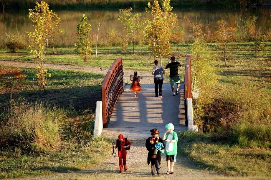 Families cross a bridge at Willow Waterhole Conservation Reserve. Photo: Karen Warren, Staff / © 2014 Houston Chronicle