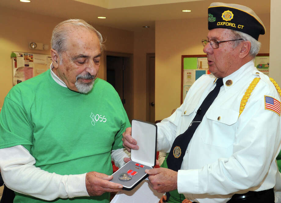 Vahan Hovey, left, of Oxford, a World War II veteran, receives his Bronze Star Medal from Henry Rotzal, Commander of Oxford American Legion Post 174 during a ceremony at the Oxford Senior Center Nov. 6, 2014. Hovey served in the U.S. Army. Photo: Ned Gerard / Connecticut Post