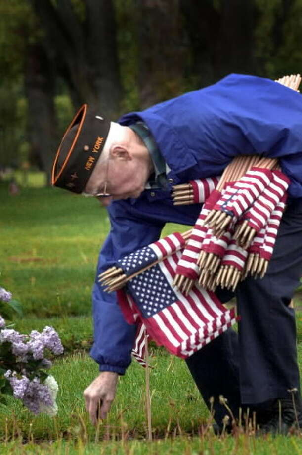 World War II veteran Norman Jensen places American flags on the headstones of veterans in Evergreen Memorial Park in May 2003. He will be the grand marshal for Albany's 59th annual Veterans Day parade on Tuesday, Nov. 11. (Times Union archive photo)