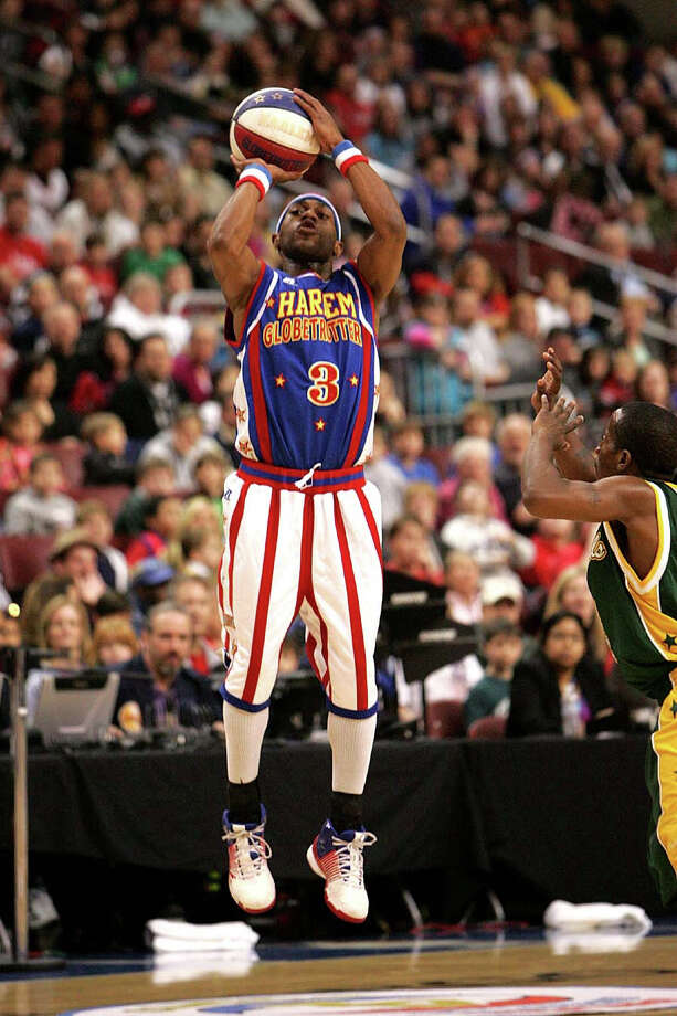 "Tay ""Firefly"" Fisher, a member of the Harlem Globetrotters, shoots a four pointer from 35-feet at a recent game.The Globetrotters will be in Bridgeport on Friday, Nov. 14, to play a game against the Washington Generals that will be taped and aired on ESPN in December. Photo: Contributed Photo / Connecticut Post Contributed"