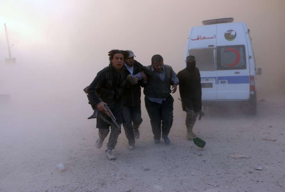 Fighters from the al Qaeda-linked Al-Nusra Front help a wounded man following an air attack by government planes. Photo: FADI AL-HALABI / AFP/Getty Images / AFP
