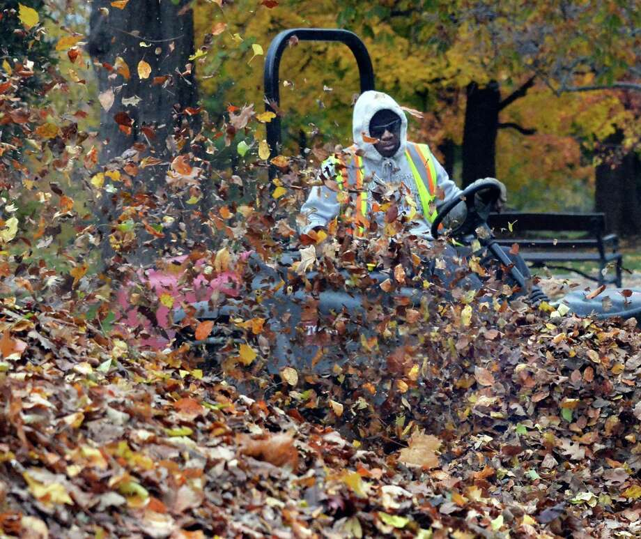 Albany City Department of General Services' Mack Lawson blows leaves into a pile for pickup in Washington park Thursday Nov. 6, 2014, in Albany, NY.  (John Carl D'Annibale / Times Union) Photo: John Carl D'Annibale