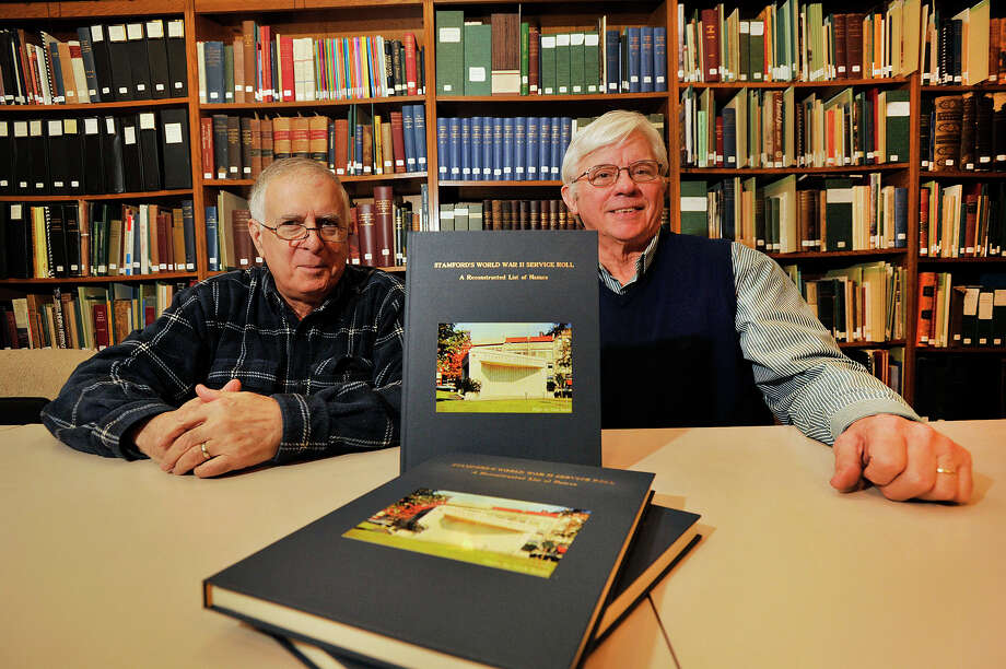 "Volunteers Ron Marcus, left, and Dan Burke display their new book ""Stamford's World War II Service Roll: A Reconstructed List of Names"" at the Stamford Historical Society in Stamford, Conn., on Thursday, Nov. 6, 2014. They say it took almost four years to collect over 10,000 names of Stamford residents who served in the military and Merchant Marines. Photo: Jason Rearick / Stamford Advocate"