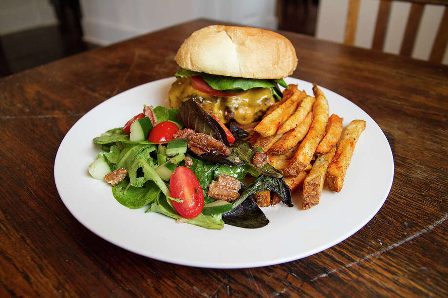 The Off-Broadway Burger features an 8-ounce hand-formed beef patty, housemade fries and a house salad with mixed greens, tomatoes and candied pecans. Photo: Alma E. Hernandez / Alma E. Hernandez / For The Express-News